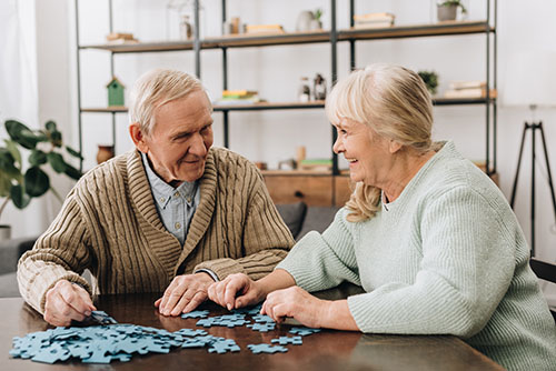 senior man and woman doing jigsaw puzzle at senior assisted living facility