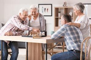 seniors playing chess enjoying their residential senior living options in college park in