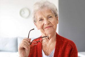 senior woman holding glasses thinking about senior living programs in bradenton fl