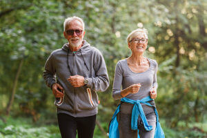 two seniors jogging in the woods during Senior Living Health Programs in college park in