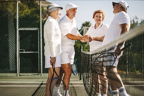 men shaking hands after a couple's tennis match of senior living community events