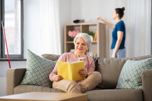 senior reading while woman cleans for Senior Living Housekeeping Services