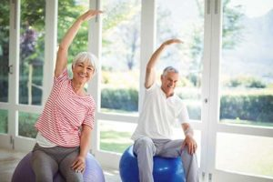 discovery-commons-cypress-point-amenities-senior-man-and-woman-stretching-on-exercise-balls