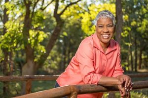 senior woman outside in nature smiling at camera