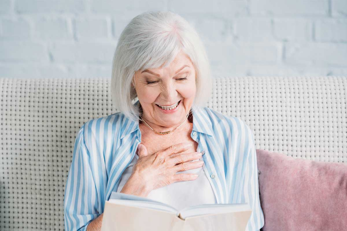 discovery-commons-cypress-point-feature-2-senior-woman-sitting-on-couch-smiling-reading-book