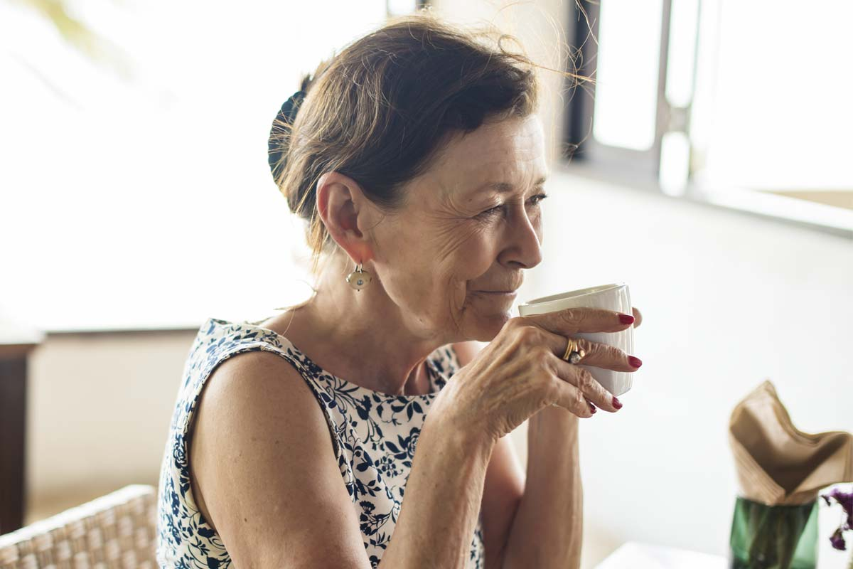 discovery-commons-cypress-point-feature-3-senior-woman-holding-teacup-at-table