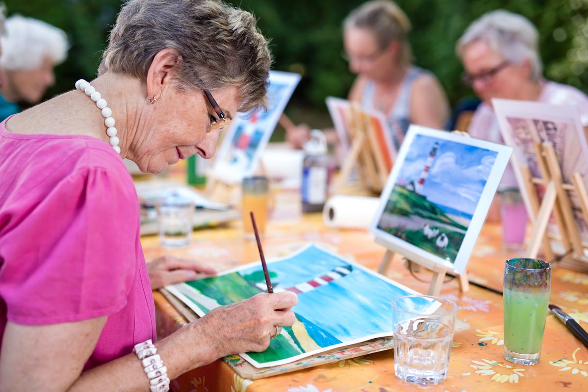 discovery commons cypress point feature 4 group of seniors painting pictures at long table outside