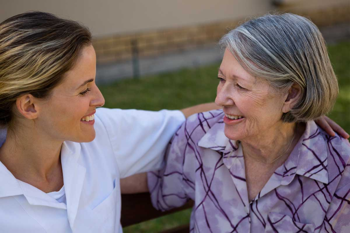 discovery-commons-cypress-point-feature-5-nurse-sitting-on-bench-with-arm-around-senior-woman's-shoulder-smiling