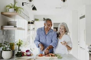 discovery-commons-cypress-point-senior-living-programs-senior-couple-chopping-vegetables-in-kitchen-smiling